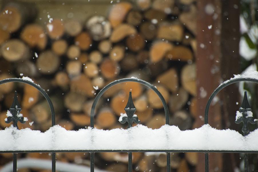 Sneeuw valt op een hekwerk