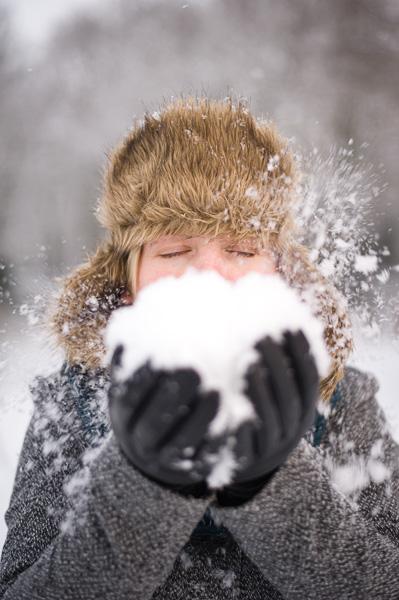 Meisje blaast sneeuw weg