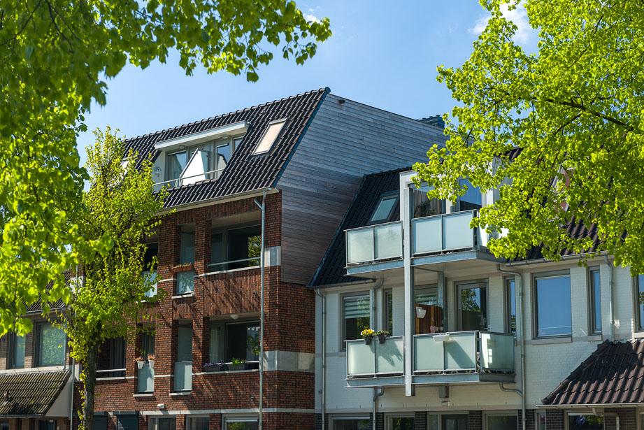 Nieuwbouwproject in Uden met groene bomen en blauwe lucht